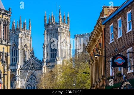 York, North Yorkshire / England: Imposing Gothic facade of York Minster with Thomas's of York pub with a sign on the right seen from Museum Street.
