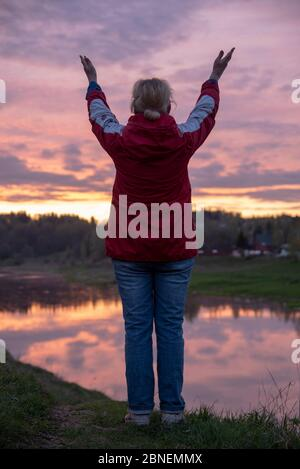 Photo of a woman standing on a hill above a river, against a bright sunset.  - Stock Photo