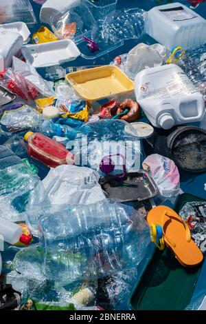 Plastic garbage floating in the ocean. The Covid-19 crisis has spurred rapid production of surgical masks, gloves, and other protective equipment. Stock Photo
