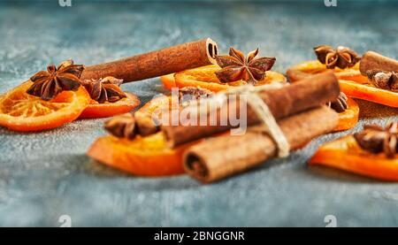 Slices of dried oranges or tangerines with anise and cinnamon, on a blue background. Vegetarianism and healthy eating. - Stock Photo