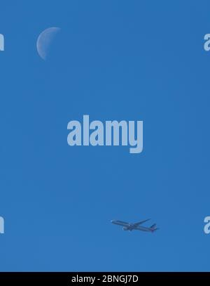 London, UK. 15 May 2020. 43.6% Waning Crescent Moon in clear blue sky over London as an American Airlines flight from Chicago arrives for final approach to Heathrow Airport on day 53 of Coronavirus lockdown. Credit: Malcolm Park/Alamy Live News - Stock Photo