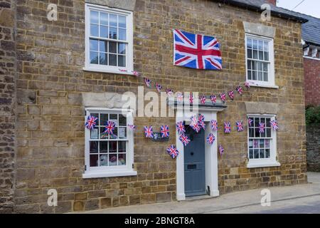 Stone built cottage, decorated with Union Jack bunting for VE Day 75th anniversary celebrations, Little Houghton, Northamptonshire, UK - Stock Photo