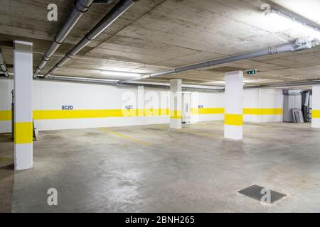 Common garage for parking cars in a multi-storey building with sewer pipes.