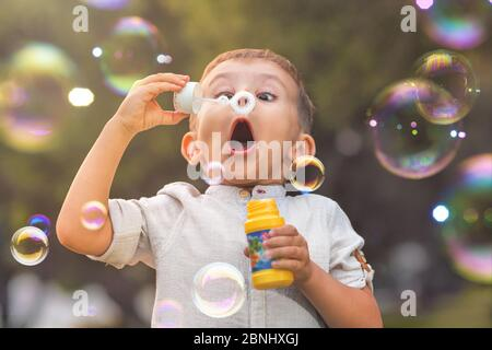 A child with an open mouth and big eyes blows colorful soap bubbles in nature.