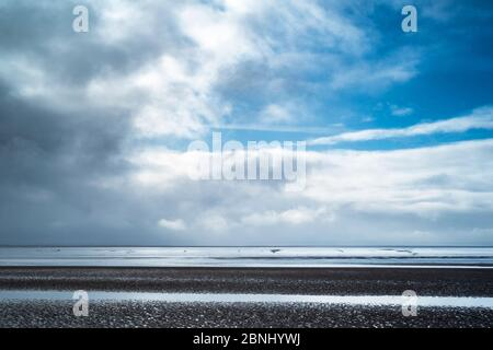 Pastel shades of sea and sandy beach of the Bristol Channel at Burnham-on-Sea sea shore, Somerset, UK