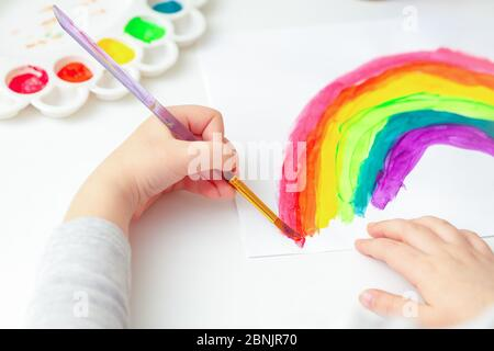 Top view of hands of child drawing a rainbow with brushes and paints on white paper. - Stock Photo