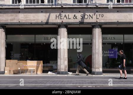 People walking past a cardboard homeless shelter outside a furniture store in Tottenham Court Road, London, after the introduction of measures to bring the country out of lockdown. - Stock Photo