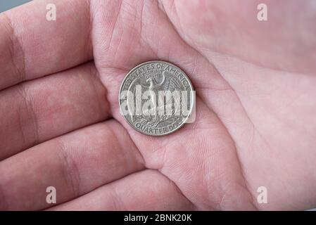 A man holding silver American quarter dollar coin, 25 cents, USA - Stock Photo