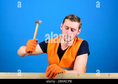 Handcrafting concept. Man, labourer, handyman in bright vest and protective gloves handcrafting, blue background. Carpenter, handsome construction man using hammer to nail together wood - Stock Photo