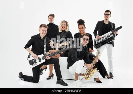 Multiracial music band on a white background. A group of international musicians rehearsing a concert performance. Vocalist, ram, guitarist