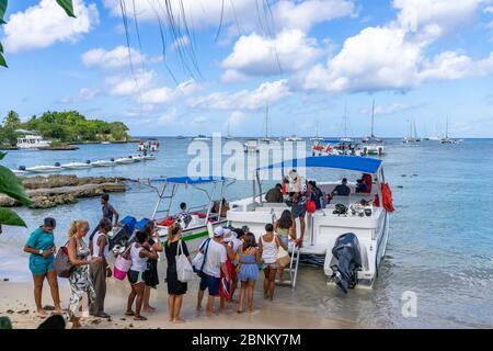 America, Caribbean, Greater Antilles, Dominican Republic, La Altagracia Province, Bayahibe, Tourists board a tour boat on Bayahibe Beach - Stock Photo