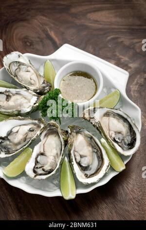 Six fresh oysters with lime wedges and citrus vinaigrette sauce - Stock Photo