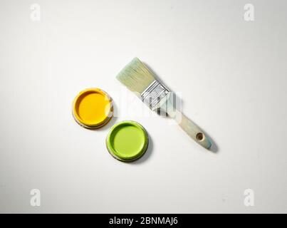 User and washed out wooden brush with two lids of paint cans, yellow and green on a white background