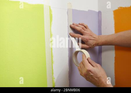DIY wall design 01, step-by-step do-it-yourself production, vertical colored stripes in the lower wall area, step 04 masking the pencil lines with painter's tape (crepe) - Stock Photo