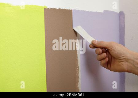 DIY wall design 01, step-by-step do-it-yourself production, vertical colored stripes in the lower wall area, step 07: Peel off the masking tape when the paint is still slightly damp - Stock Photo