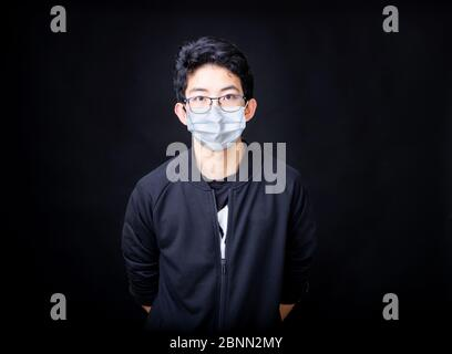 Portrait of young Asian Chinese man wearing medical mask on black background. Concept of protecting your health against Covid-19 Coronavirus pandemic. - Stock Photo