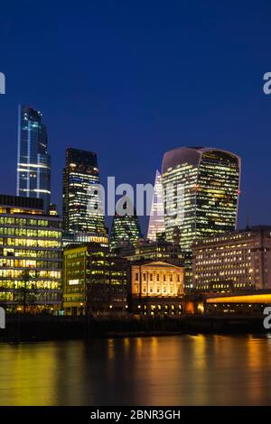 England, London, City of London Skyline showing Modern Skyscrapers and London Bridge and River Thames at Night - Stock Photo