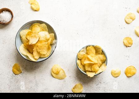 Homemade potato chips in bowls. Crispy potato chips on white background, top view, copy space. - Stock Photo