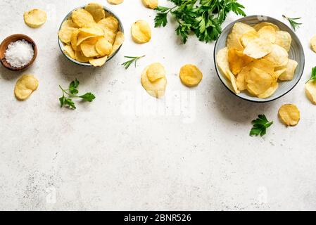Oven baked  potato chips in bowls. Homemade crispy potato chips on white background, top view, copy space. - Stock Photo