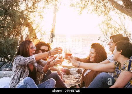 Group of middle age young adult women having fun together toasting and clinking with wine glasses at the beach during a golden sunset enjoying outdoor leisure activity or vacation - Stock Photo