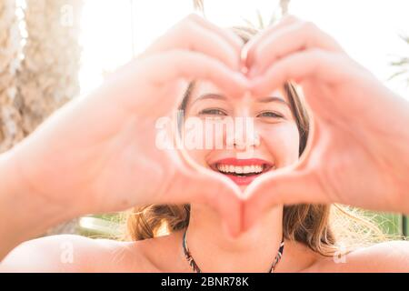 Close up portrait of beautiful.  caucasian young woman doing love hearth sign with hands at the camera - sun bright background and joyful happiness people concept - Stock Photo