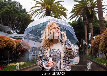 Attractive and cheerful fashion trendy middle age young caucasian woman walking in the city under the rain with a transparent umbrella - cold season concept enjoying the urban park