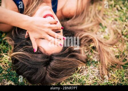 Laugh and cheerful people young caucasian woman lay down on the grass and laughing a lot with hand on face - beautiful healthy long brown hair and happiness joyful concept - Stock Photo
