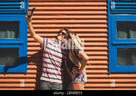 Young beautiful caucasian people couple take a slefie picture together with a kiss and smile - technology and social media pictures concept - coloured background - Stock Photo