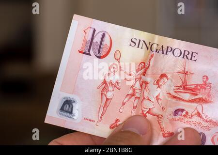 Persons hand giving the Currency of the Singapore - One red ten dollar note spread out on a brown background. Money exchange. - Stock Photo