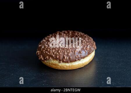 Sweet donut on black background. Tasty, fresh sprinkled donut - Stock Photo