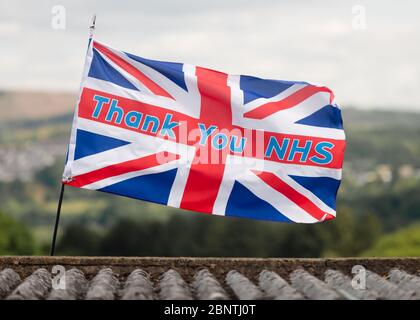 Newport, Wales, UK. 16th May, 2020. A union jack flag with the slogan thank you NHS, blows in the wind above a rooftop during the Covid-19 coronavirus pandemic in the UK. Credit: Tracey Paddison/Alamy Live News - Stock Photo
