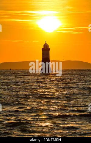 Sunrise over Trwyn Du lighthouse at Penmon on Anglesey in North Wales - Stock Photo