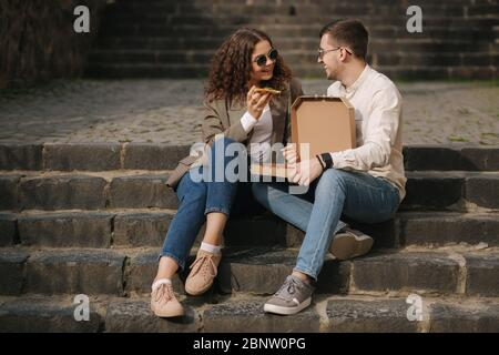 Young couple sitting on stairs outdoor and eating pizza. Handsome man with beaufitul woman taste pizza with vegetables. Vegan fast food