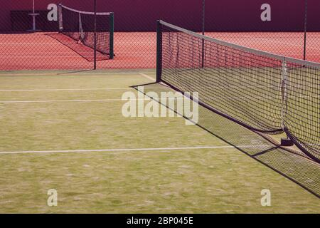 Tennis courts, green and red color. Tennis net in perspective. Nobody in the picture. - Stock Photo