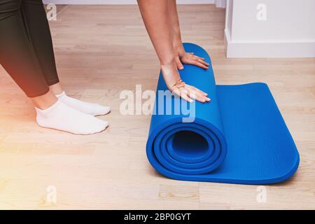 Close-up of woman folding blue yoga or fitness mat after working out at home - Stock Photo
