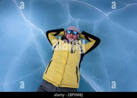 Happy girl in yellow black jacket, grey pants, blue mirrored sunglasses and pink hat lying on the blue cracked ice of Lake Baikal. Top view - Stock Photo