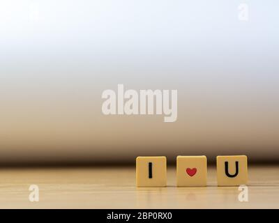 i love u word written in  cube on wooden floor on white background, letter blocks arranges into I LOVE U words, for adding text or other images or des - Stock Photo