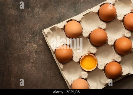 Brown eggs in a carton, one egg is broken. View from above