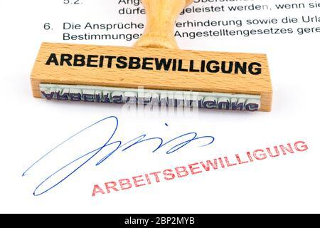 Ein Stempel aus Holz liegt auf einem Dokument. Aufschrift Arbeitsbewilligung