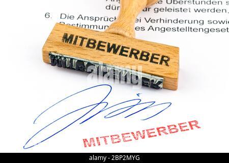 Ein Stempel aus Holz liegt auf einem Dokument. Aufschrift Mitbewerber