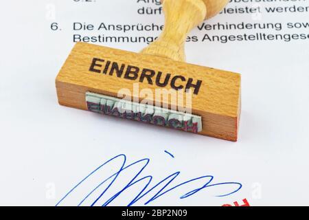 Ein Stempel aus Holz liegt auf einem Dokument. Aufschrift: Einbruch
