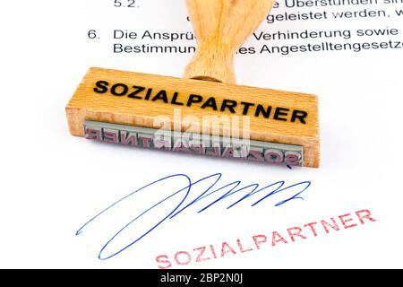 Ein Stempel aus Holz liegt auf einem Dokument. Aufschrift: Sozialpartner