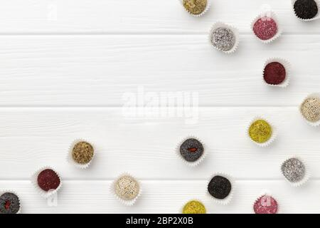 Many colorful vegan candies energy balls on white wooden table