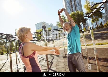Staying healthy. Active mature family couple in sportswear warming up together at outdoor gym in the morning, aged couple doing stretching exercises