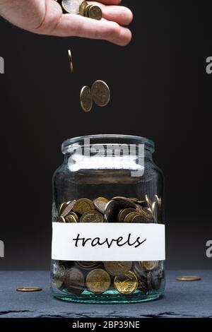 Coins in a jar with travels text on a white label. Caucasian man throwing money from above. Savings abstract concept. Copy space. Vertical orientation