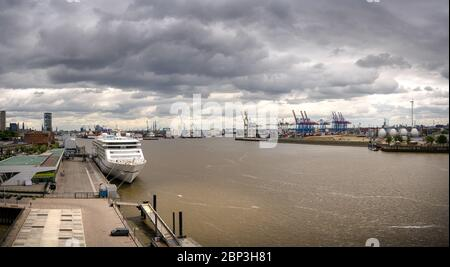 Panorama of a container terminal and industrial facilities in the port of Hamburg with a cruise liner - Stock Photo