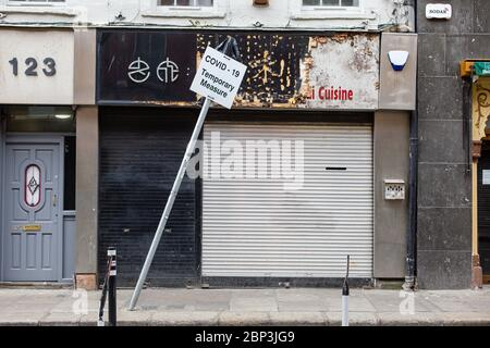 Closed down shop on Capel Steet in Dublin and leaning sign - Covid-19 Temporary Measure. Coronavirus outbreak lockdown economic impact, Ireland.