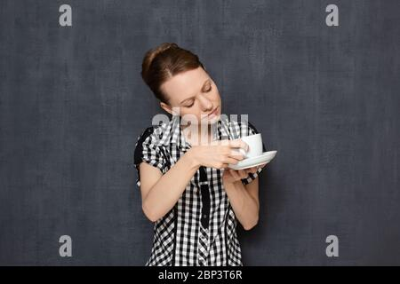 Studio portrait of focused curious young blond woman wearing checkered shirt, looking attentively and with interest inside cup and inspecting sediment