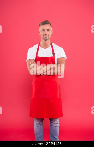 hospitable and confident husband. man in apron at kitchen. handsome janitor wear uniform for cleaning. friendly smiling bartender. Professional cleaning. household and people concept. - Stock Photo