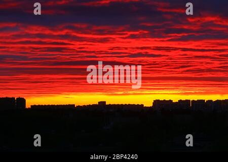Bright fiery sunset over the dark silhouettes of houses, sky in the clouds, multi-colored paints . - Stock Photo
